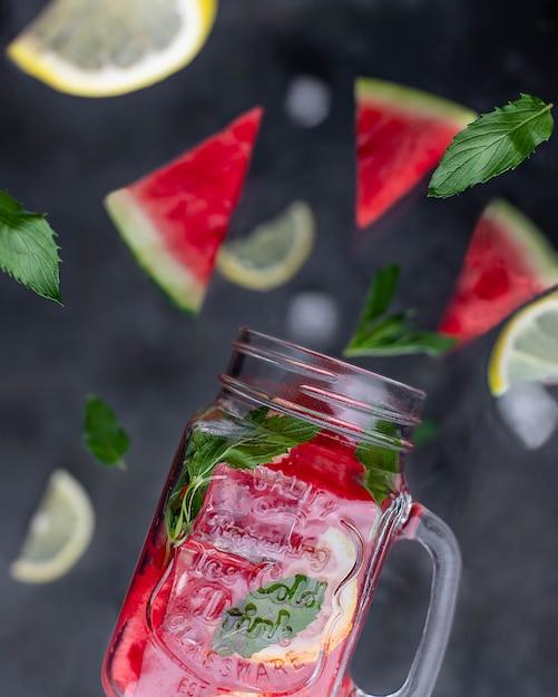 Limonata in un bicchiere con anguria limone e menta su uno sfondo scuro Foto Premium