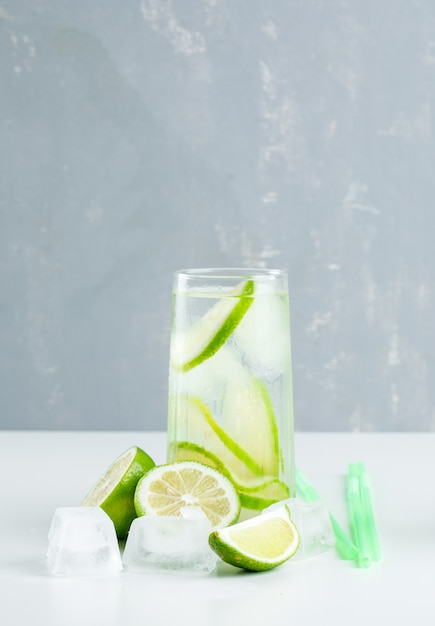 Limonata in un bicchiere con limone, cannucce, cubetti di ghiaccio vista laterale su bianco e gesso Foto Gratuite