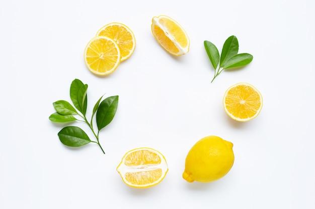 Limone e fette con foglie isolate su bianco. Foto Premium