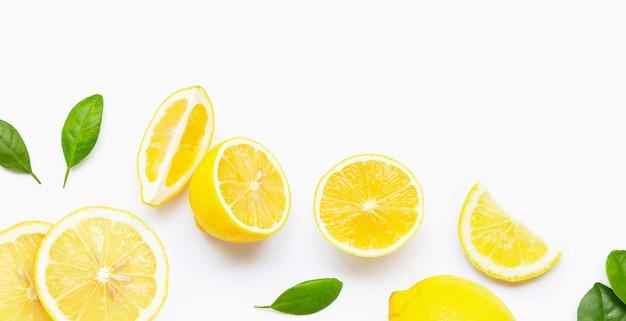Limone e fette freschi con le foglie isolate su bianco. Foto Premium