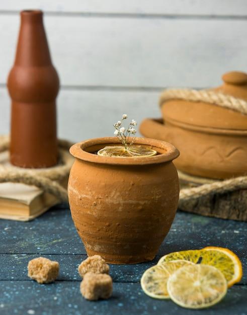 Limone e fiori in vasino sul tavolo Foto Gratuite