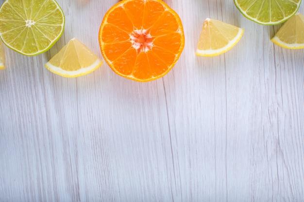 Limoni a fette agrumi limetta arancione vista dall'alto sulla superficie in legno Foto Gratuite