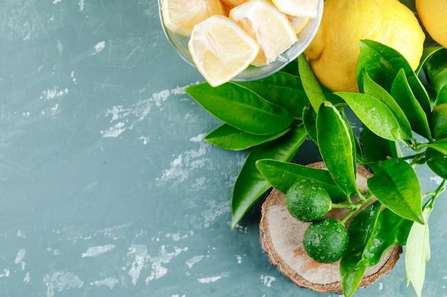 Limoni con fette, foglie, tavola di legno vista dall'alto su una superficie di gesso Foto Gratuite