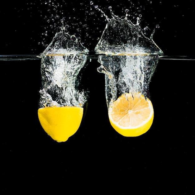 Limoni divisi in due che cadono nella spruzzata dell'acqua sopra fondo nero Foto Gratuite