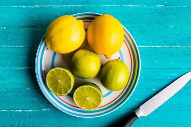 Limoni e lime sul piatto sulla tavola Foto Gratuite