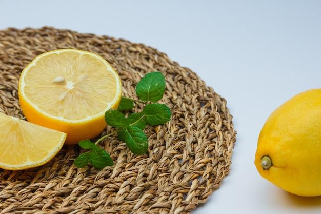 Limoni freschi con le foglie sulla stuoia bianca e di vimini Foto Gratuite