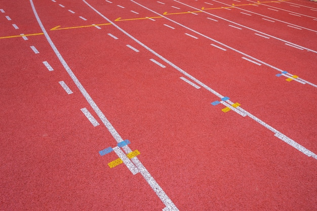 Linee bianche di stadio e struttura di piste da corsa in gomma rossa da corsa Foto Premium