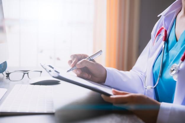 Lista di controllo femminile della tenuta della mano di medico alla tavola dell'ufficio con il computer. concetto di assistenza sanitaria. Foto Premium