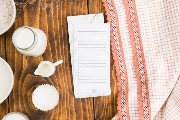 Lista vuota sul blocco note con barattolo di latte e muffa della torta della tazza sulla scrivania in legno vicino tovaglia Foto Gratuite