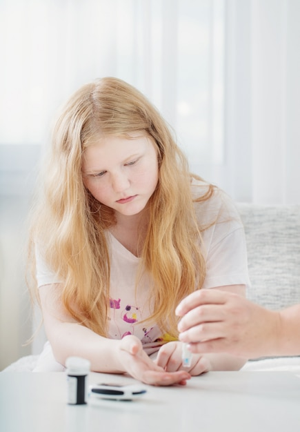 Livello di zucchero nel sangue di misurazione della ragazza teenager con il glucometro Foto Premium