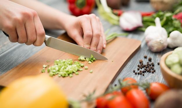 Lo chef di cucina taglia gli alimenti tagliati prepara le verdure Foto Premium