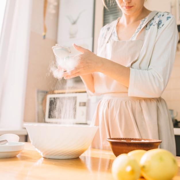 Lo chef femminile in una cucina prepara l'impasto dalla farina per fare la torta Foto Gratuite
