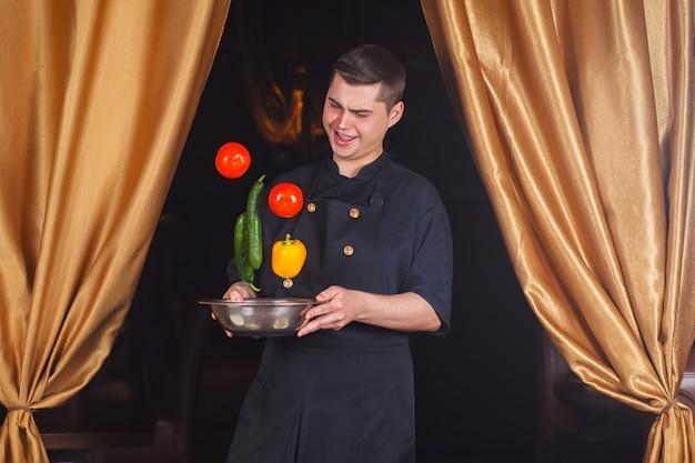Lo chef getta verdure fresche. Foto Premium