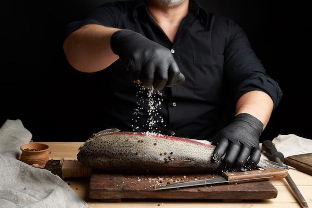 Lo chef in camicia nera e guanti in lattice nero prepara il filetto di salmone Foto Premium