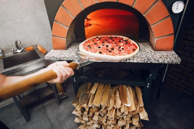 Lo chef in cucina prepara la pizza Foto Gratuite