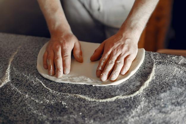 Lo chef in uniforme bianca prepara una pizzaa Foto Gratuite