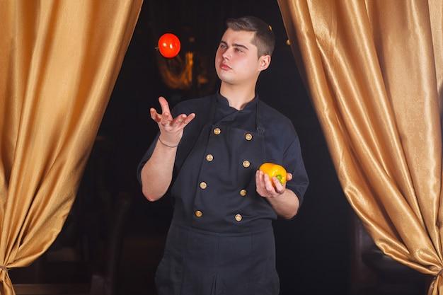 Lo chef lancia un pomodoro. Foto Premium