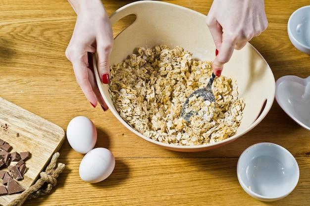 Lo chef prepara biscotti di farina d'avena, mescola ingredienti: fiocchi d'avena, burro, zucchero, uova, cioccolato. Foto Premium