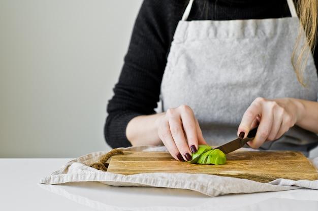Lo chef sbuccia l'avocado su un tagliere di legno. Foto Premium