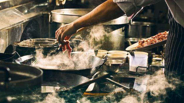 Lo chef sta cucinando manzo nel wok Foto Premium