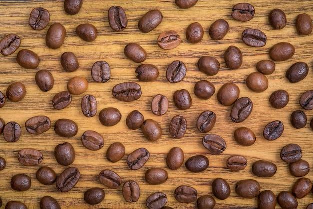Lo sfondo dei chicchi di caffè tostato è marrone su tavole di legno Foto Premium