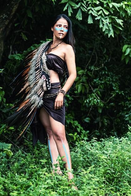 Lo sfondo di disegno di arte astratta di bella donna ha messo piume di copricapo di uccelli sulla sua spalla Foto Premium