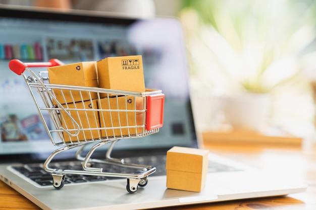 Lo shopping online e il concetto di consegna, scatole del pacchetto di prodotti nel carrello e laptop Foto Premium