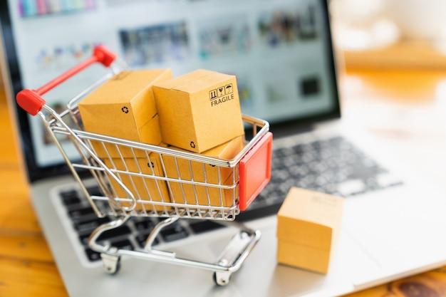 Lo shopping online e il concetto di consegna, scatole pacchetto di prodotti nel carrello e computer portatile. Foto Premium