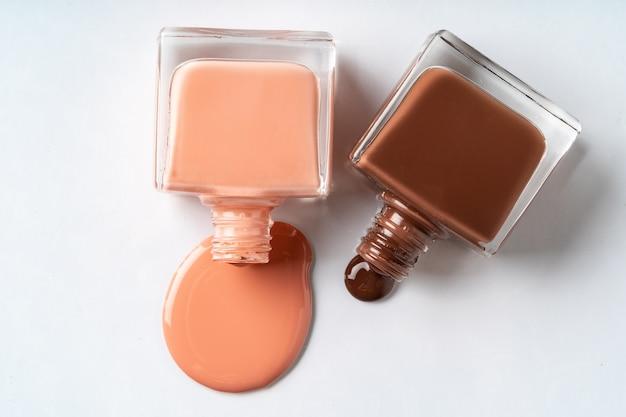 Lo smalto di colori nudo si è rovesciato sopra fondo bianco Foto Premium