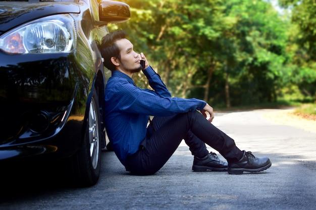 Lo smart phone della tenuta dell'uomo deludente e sedentesi all'auto ha parcheggiato sulla strada Foto Premium