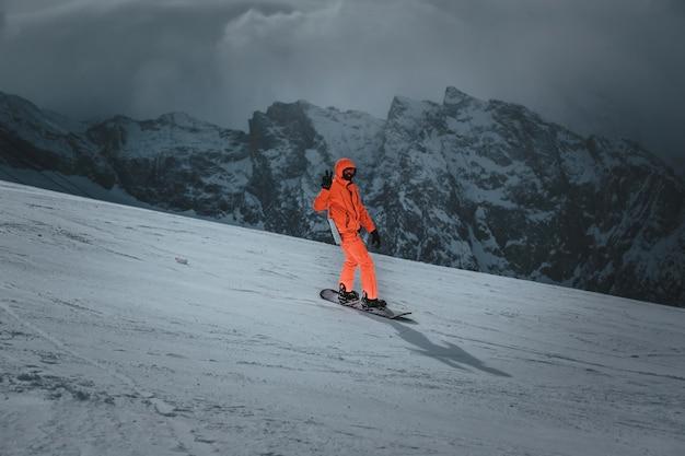 Lo snowboarder dell'uomo guida sul pendio. stazione sciistica. spazio per il testo Foto Premium