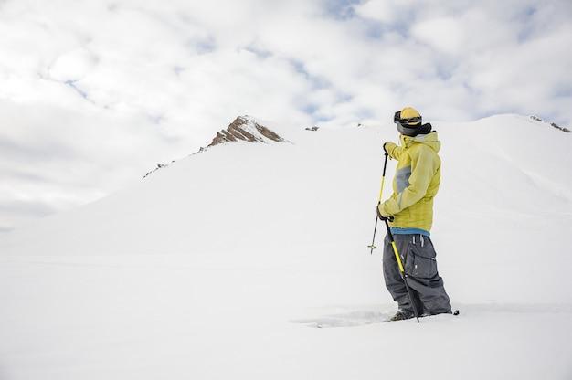 Lo snowboarder di freeride si è vestito in abiti sportivi gialli che esaminano la montagna Foto Premium
