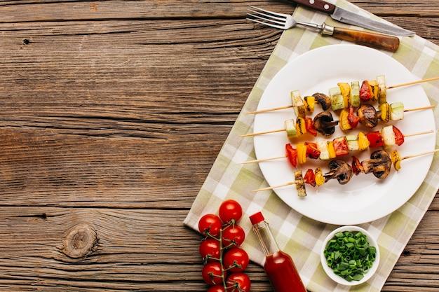 Lo spiedo arrostito di kebab è servito sul piatto bianco sopra i tavoli di legno Foto Gratuite