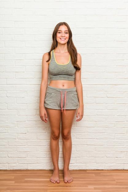 Lo sport da portare della giovane donna caucasica copre contro il muro di mattoni Foto Premium