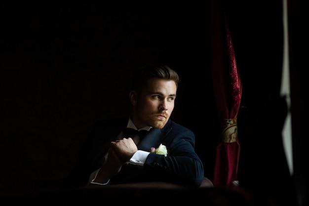 Lo sposo alla moda aspetta la sposa vicino alla finestra. ritratto dello sposo in un abito nero Foto Premium