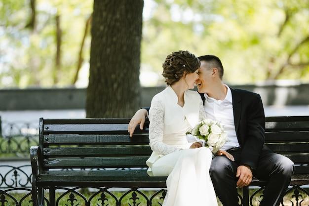 Lo sposo con la sposa si siede su una panchina e sorride Foto Gratuite