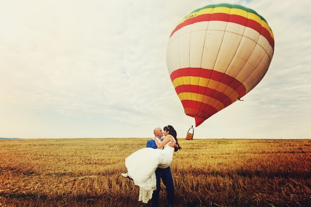 Lo sposo detiene una sposa tra le braccia mentre il vento soffia il palloncino Foto Gratuite