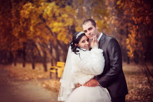Lo sposo e la sposa nel parco d'autunno camminano vicino agli alberi con foglie gialle Foto Premium