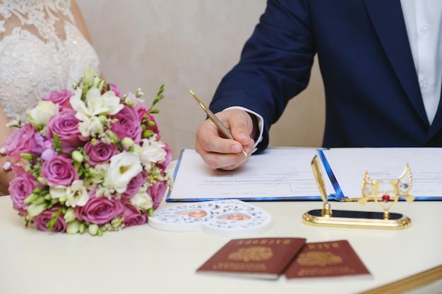 Lo sposo in un giorno del matrimonio mette una firma. cerimonia matrimoniale. Foto Premium