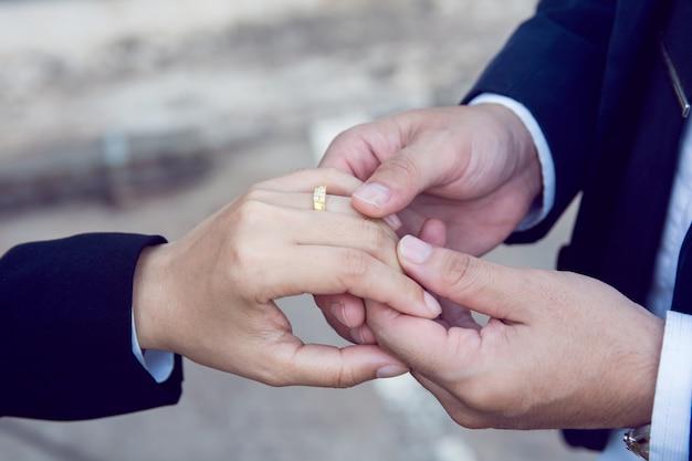 Lo sposo indossa l'anello al dito della sposa Foto Premium