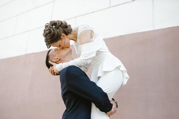 Lo sposo tiene la sposa sulle sue mani e la bacia Foto Gratuite