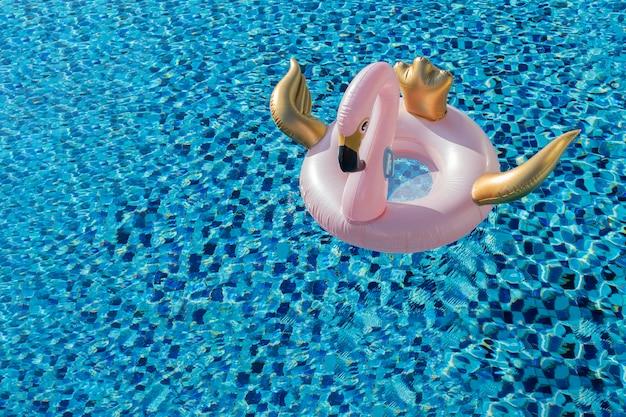 Lo stagno affascinante del fenicottero del cigno dell'oro e di rosa galleggia nella piscina blu con copyspace Foto Premium