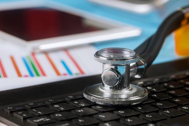 Lo stetoscopio di analisi dei dati del calcolatore sopra una tastiera di computer portatile ha utilizzato la pro compressa digitale Foto Premium