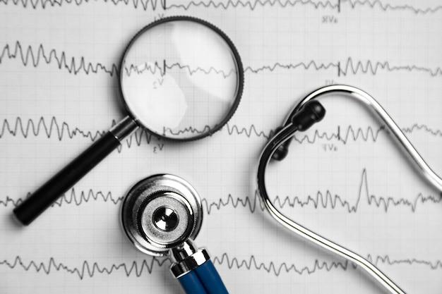 Lo stetoscopio e la lente d'ingrandimento si trovano sullo strato con la vista superiore del primo piano di ecg Foto Premium