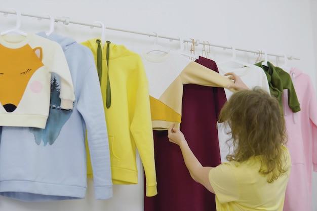 Lo stilista lavora alla nuova collezione di abbigliamento femminile in studio, sarta, sarta o sarta in piedi vicino al porta abiti Foto Premium