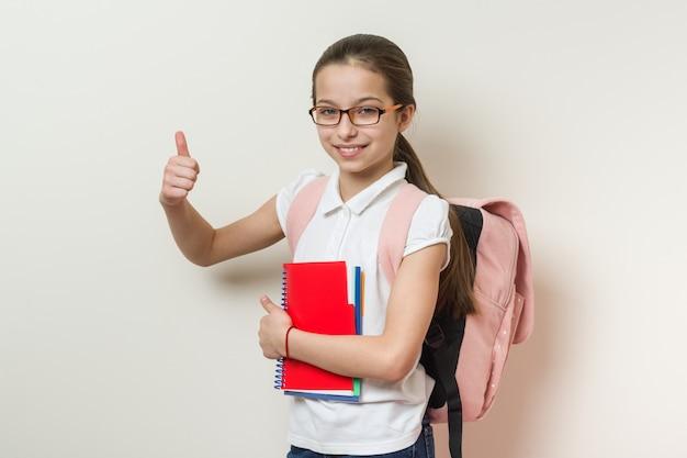 Lo studente della scuola della ragazza che mostra i pollici aumenta il segno Foto Premium