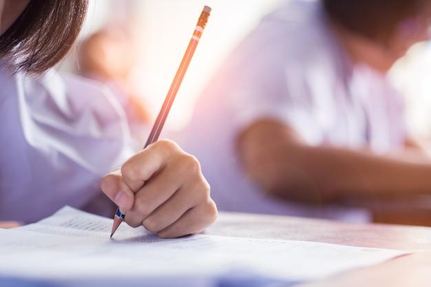 Lo studente della scuola sta prendendo l'esame e sta scrivendo la risposta in aula per il concetto del test di istruzione. Foto Premium