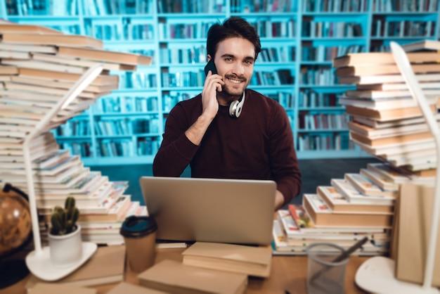 Lo studente sta usando il computer portatile e sta parlando al telefono. Foto Premium