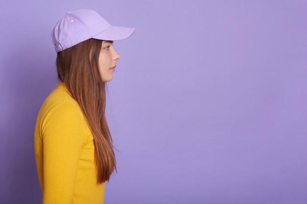 Lo studio ha sparato del berretto da baseball d'uso femminile e della camicia gialla, vista laterale della femmina attraente che guarda avanti diritto Foto Gratuite