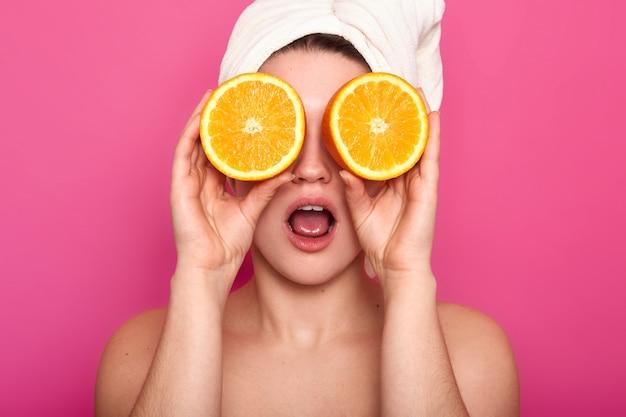 Lo studio ha sparato dell'occhio europeo scioccato giovane sembrante piacevole della donna con le arance, ha l'asciugamano bianco sulla testa. il modello con chiara pelle posa in studio isolato sul rosa. concetto di bellezza. Foto Gratuite